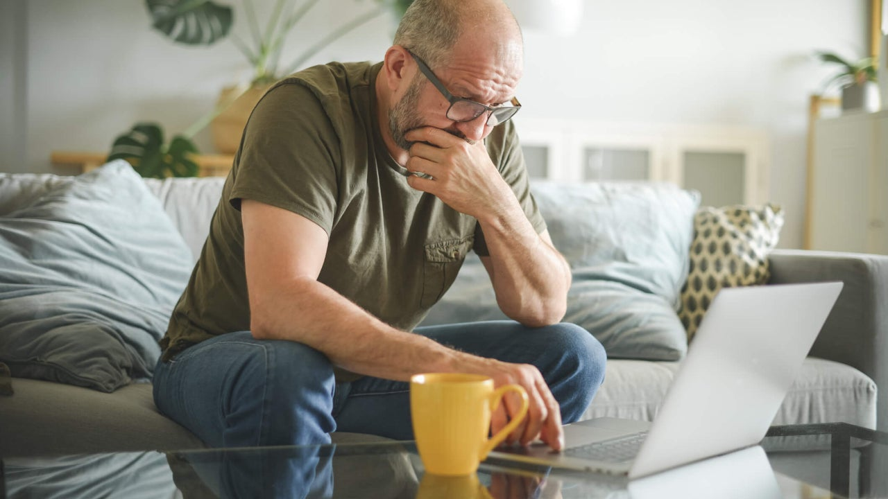 Stressed middle-aged man using laptop in living room