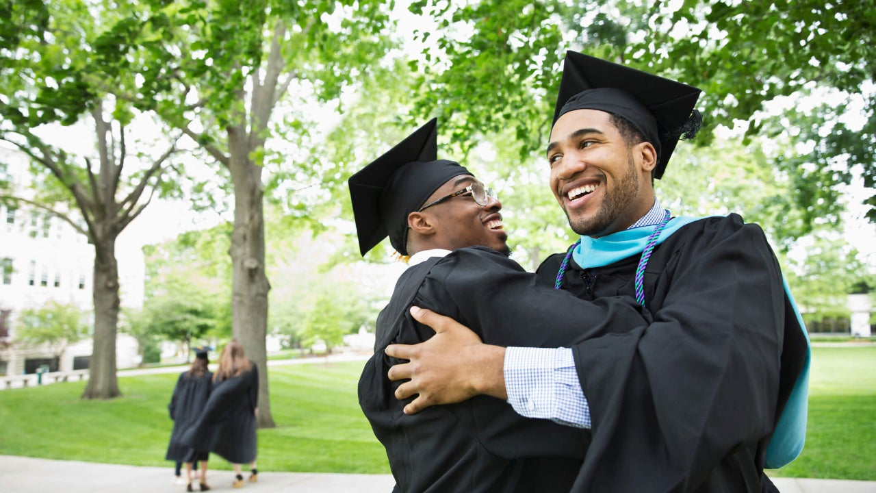 Two male college graduates in caps and gowns embrace and smile
