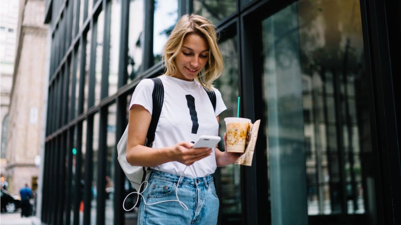 Woman walks down the street on her phone
