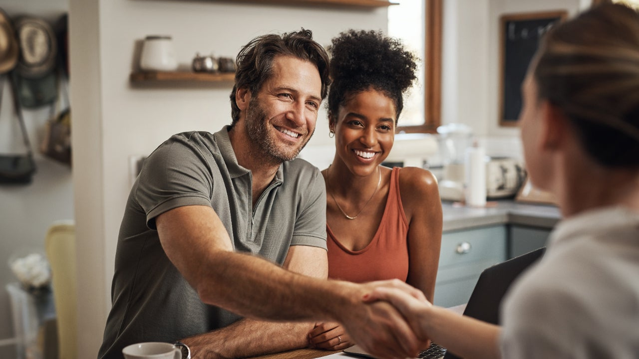 A smiling Black woman sits next to a handsome middle aged white man shaking hands with a financial advisor during a consultation at home
