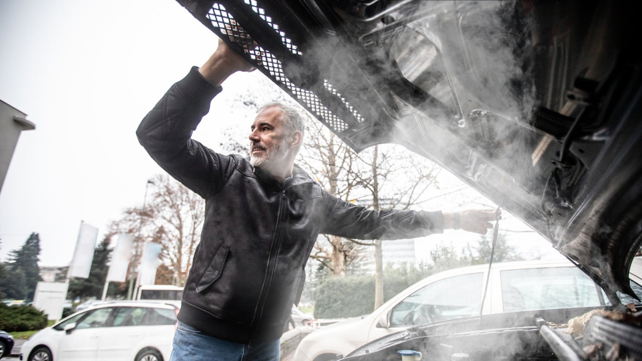 Steam Coming Out of Car Engine While Mature Man is Opening the Hood