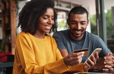Young woman uses smartphone and smiles with credit card in hand with a young man