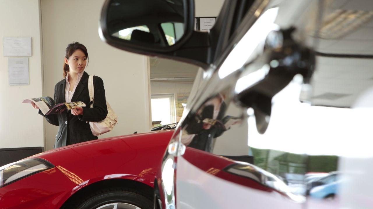 chinese female executive in car showroom