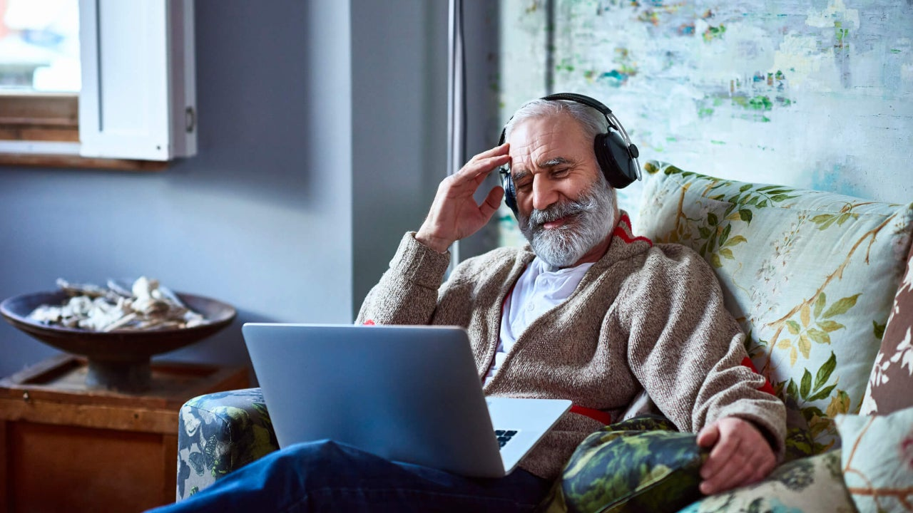 Senior man wearing headphones and using a laptop reclines in armchair as he streams a movie at home