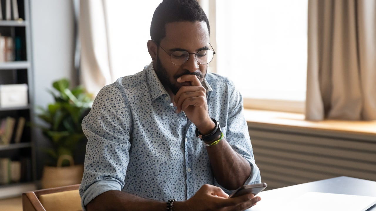 A man looks over his phone pensively