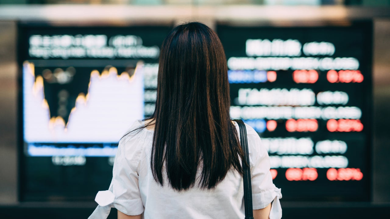 Rear view of businesswoman looking at stock exchange market display screen board in downtown financial district