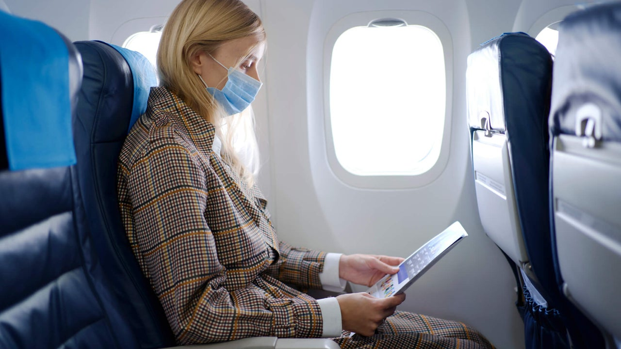 Young woman wearing mask in airplane seat looks at magazine