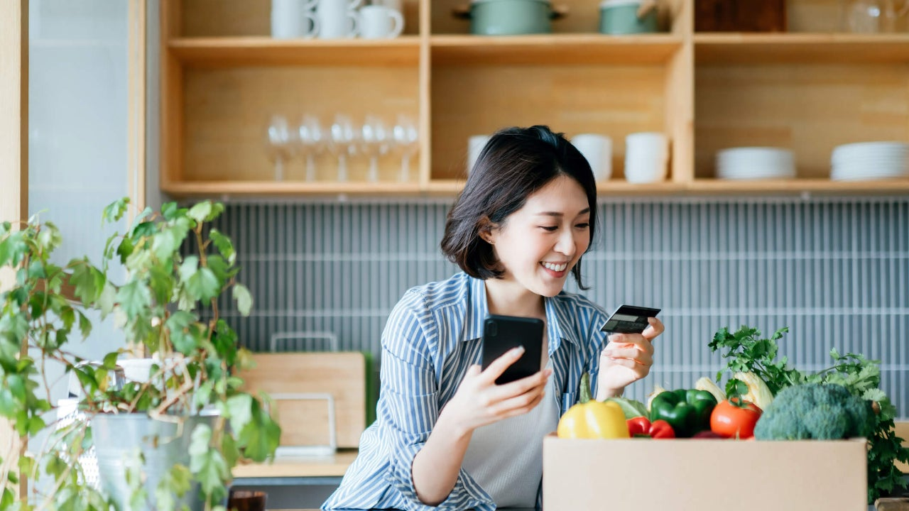 Standing woman holds smartphone and credit card at kitchen counter with box of fresh produce