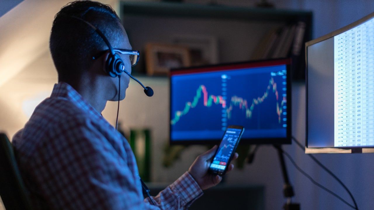 A man looks at his phone and computer screen while trading