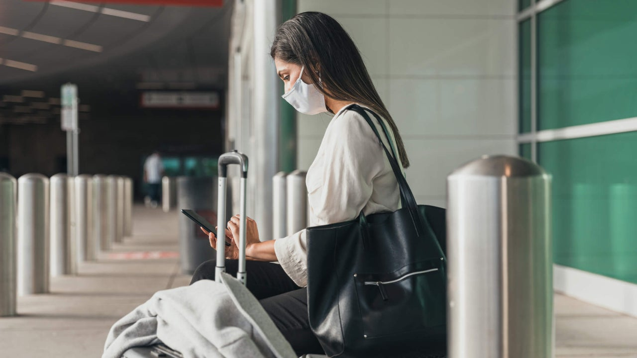 Young woman sitting outside airport terminal and wearing a mask uses her smartphone while surrounded by her luggage