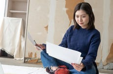 Asian entrepreneur working on floor in unfinished office space
