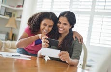 Teenage daughter and mother depositing check through smartphone at home