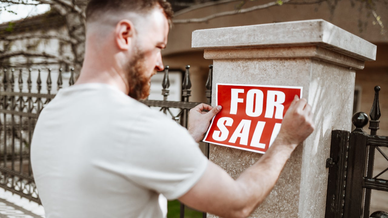 Bearded Male Sticking For Sale Sign On House Yard Post