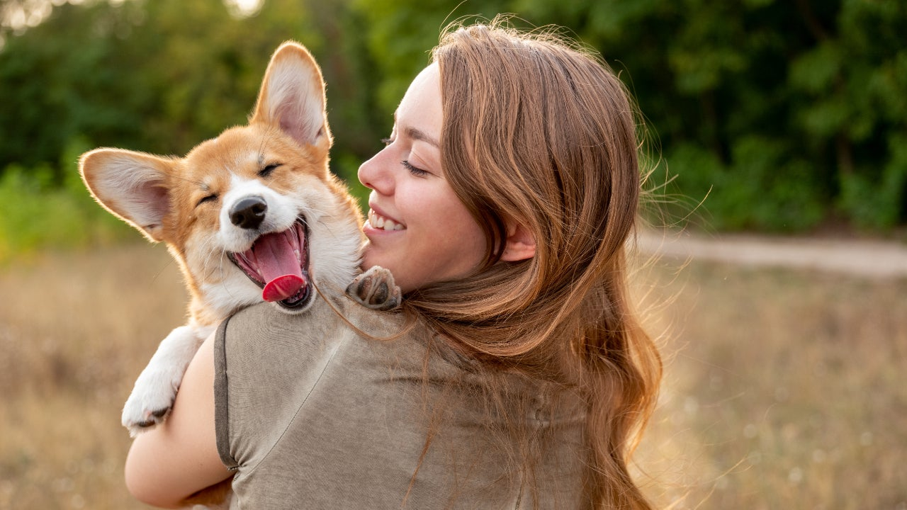 A woman holds her smiling dog