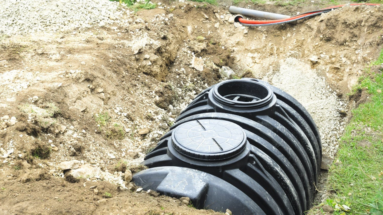 A black septic tank halfway buried in dirt outside
