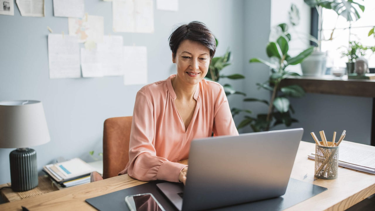Middle aged woman smiles and uses laptop in home office at desk