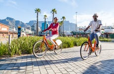 An older couple bikes through a public plaza