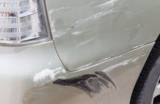 Close up of scratch in paint on white car