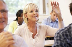 Woman in a classroom raises her hand