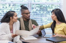 Young couple with advisor, signing paperwork