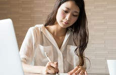 Woman filling out important paper documents