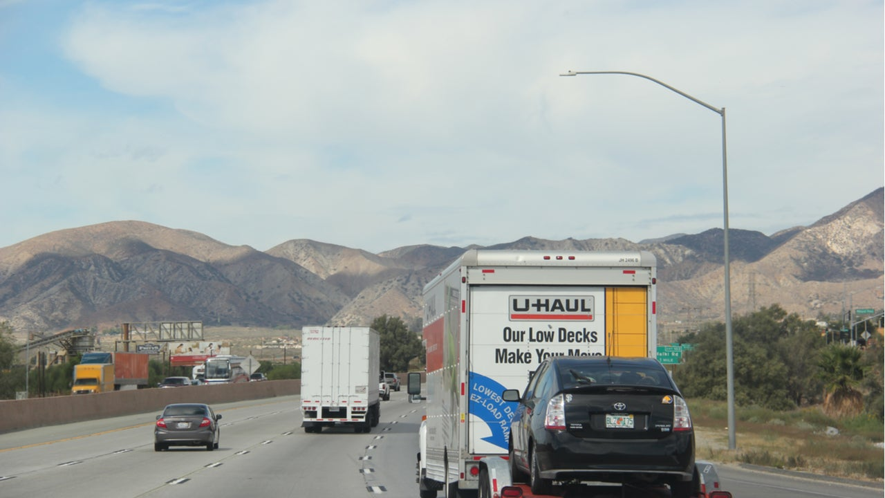 A U-Haul truck towing a car on a California highway