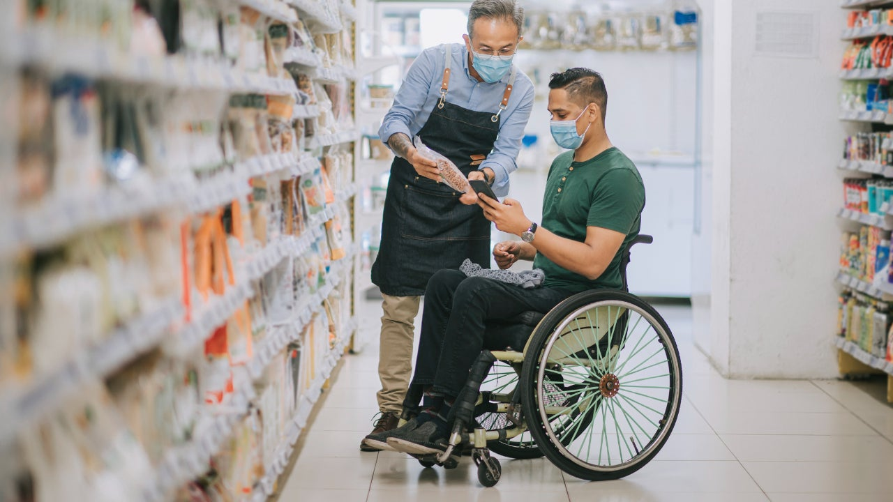 Man in wheelchair shopping in pharmacy or grocery store