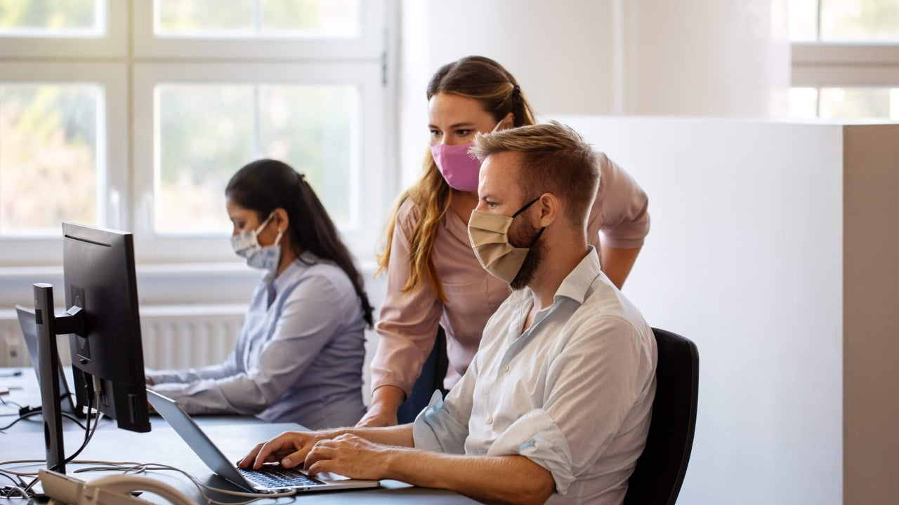 Two coworkers wearing masks in an office gather around a desktop computer and laptop