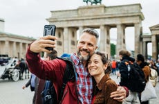 A middle-aged couple takes selfie in front of monument