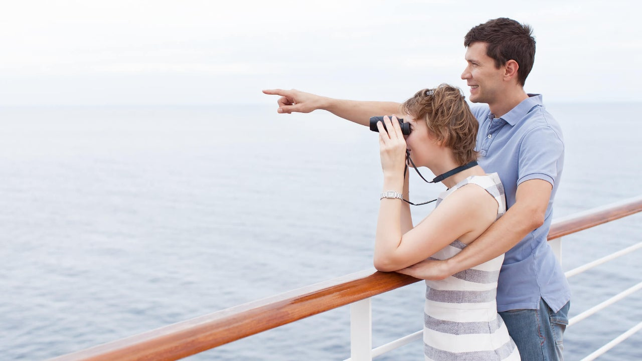 Couple on cruise ship points and looks through binoculars at the ocean