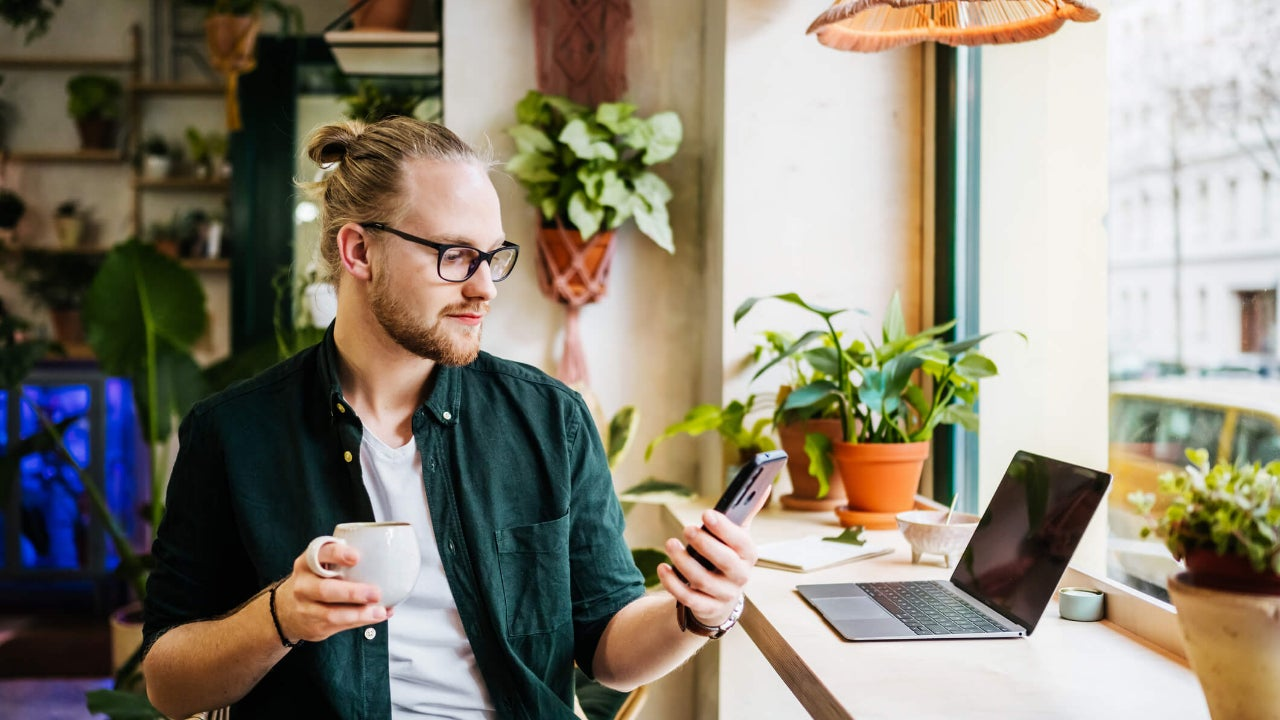 Young man looks at smartphone in cafe with his laptop in front of him