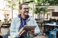 Young man at outdoor cafe smiles as he holds his tablet and credit card