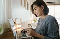 Young woman using a laptop with credit card while relaxing at home