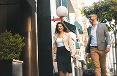 A businessman and businesswoman walk down a city street with luggage laughing