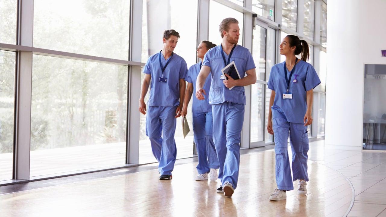 Group of nurses walk down a hallway