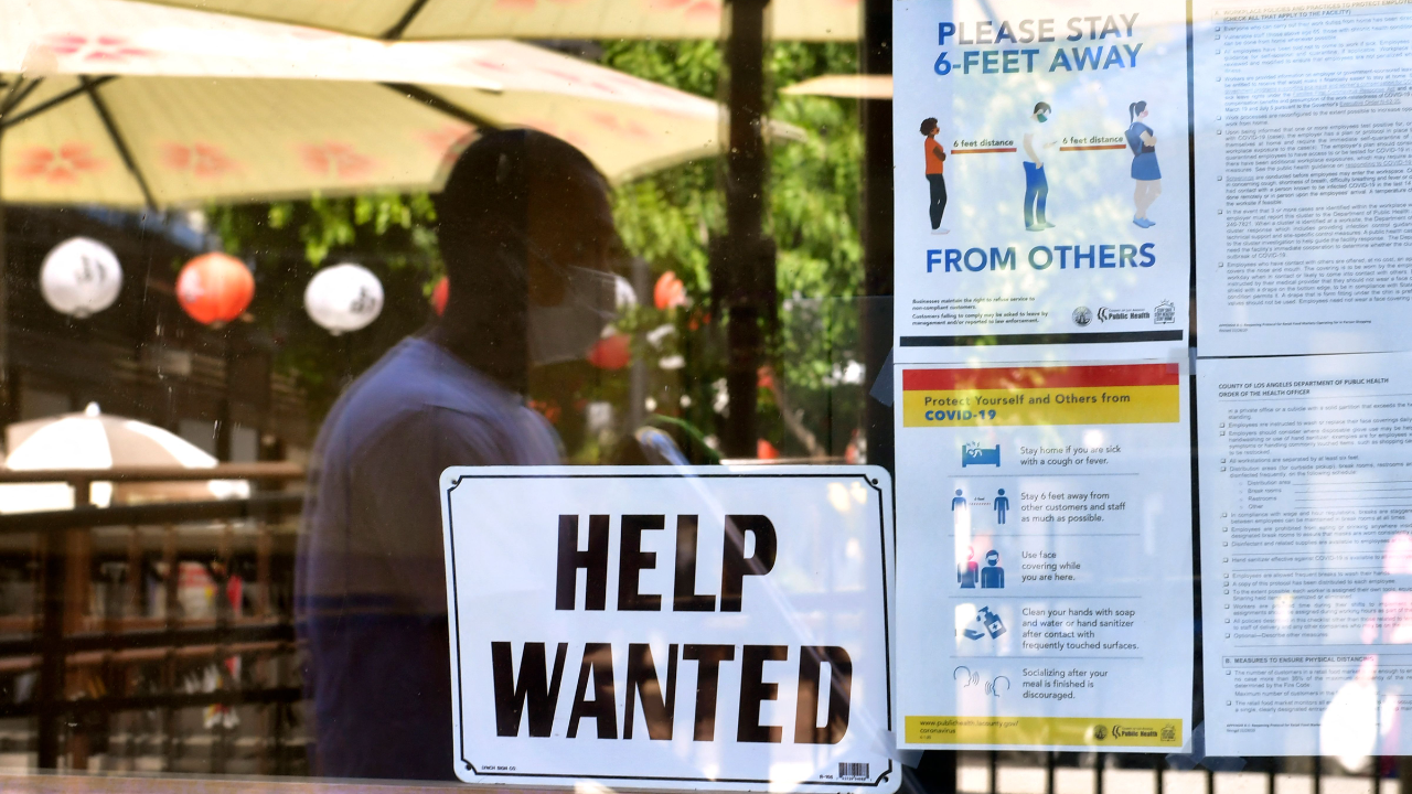 A 'Help Wanted' sign is posted beside Coronavirus safety guidelines in front of a restaurant.