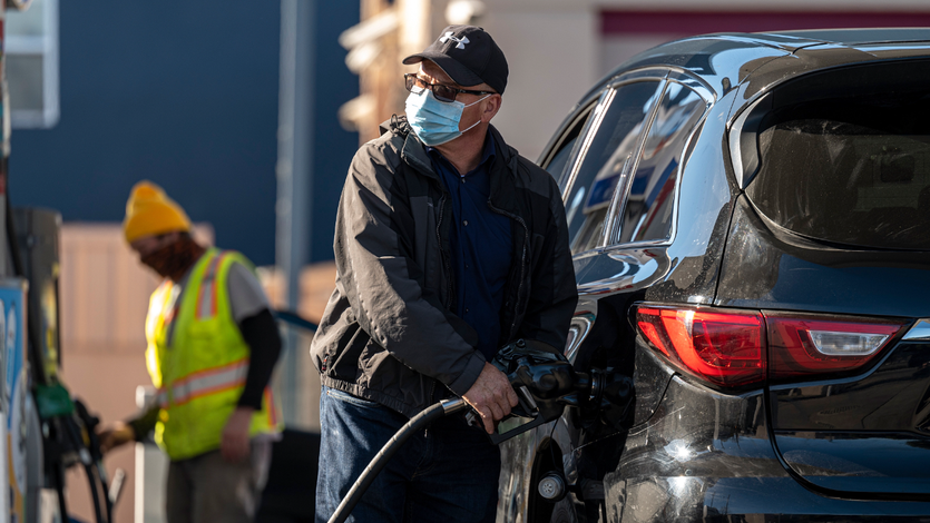 A person wearing a protective mask holds a fuel pump nozzle at a Chevron Corp. gas station in San Francisco, California.