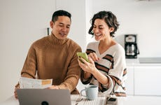 Online banking for family budget - couple in the kitchen with bills