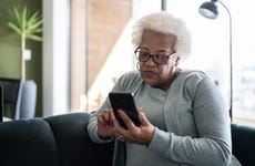 Senior woman using smartphone sitting on the couch at home
