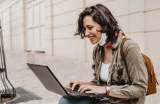 Young woman wearing face mask sits on a city curb and smiles as she uses her laptop