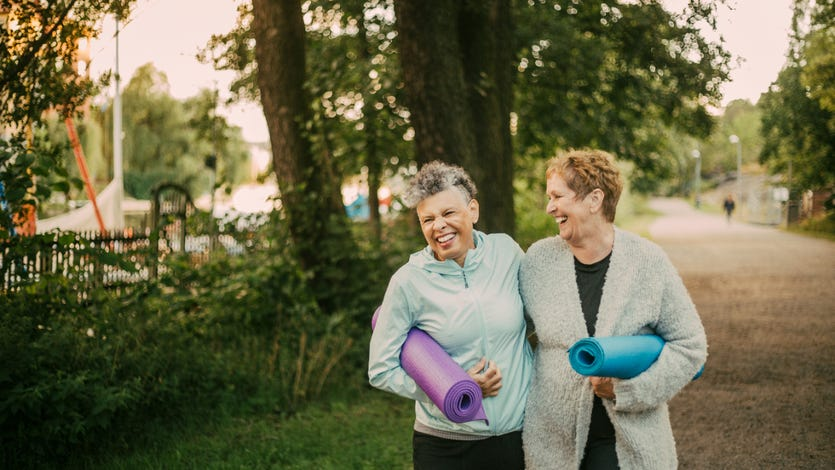 Two senior women with yoga mats walk in the park