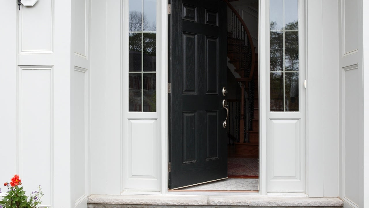 The front door of a home open slightly to the interior