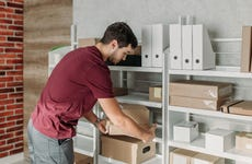 A man moves a box of documents stored on a shelf.