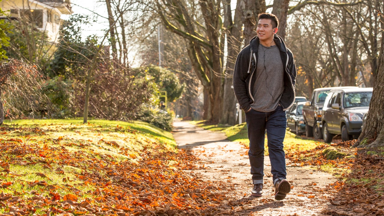 Mixed race man walking on suburban street with fall leaves on the ground