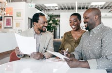 A Black couple meets with a mortgage banker.