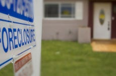 A closeup of a foreclosure sign outside of a home