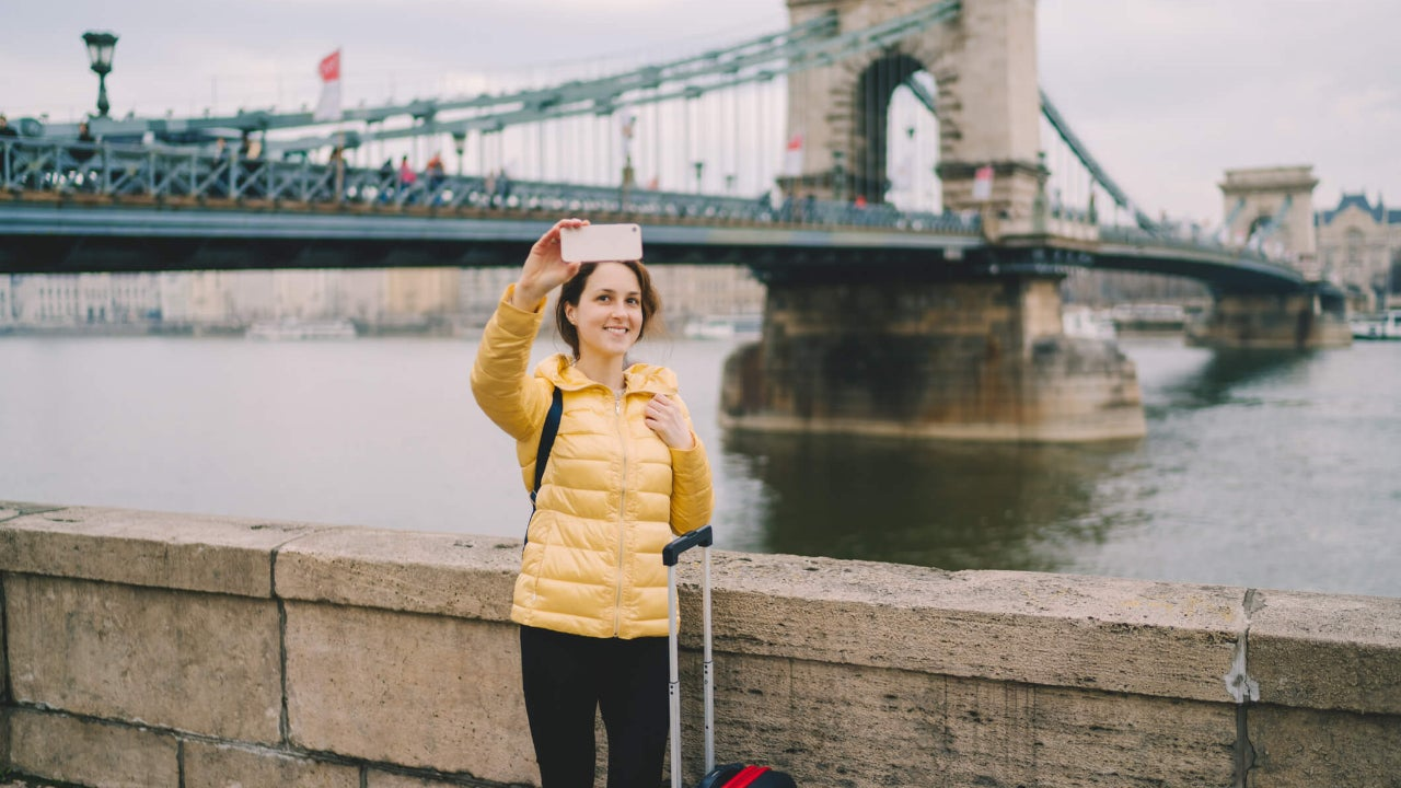 Tourist woman with suitcase takes selfie in front of a bridge in Budapest