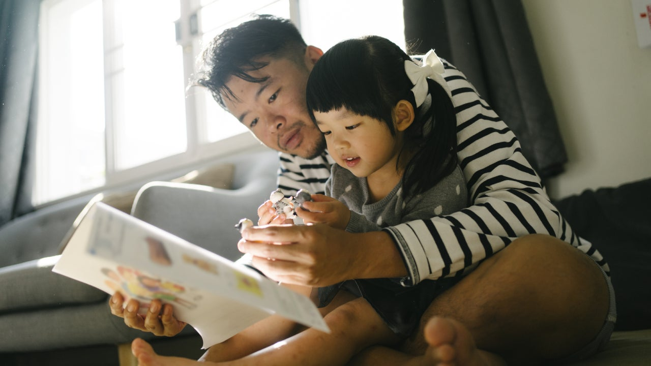 quality times father enjoyment time reading abook with daughter at home weekend activitiy